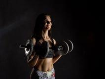 Geschiktheids sexy meisje met domoren op een donkere achtergrond Atleet die oefeningen in de gymnastiek doen Stock Afbeelding