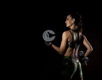 Geschiktheids sexy meisje met domoren op een donkere achtergrond Atleet die oefeningen in de gymnastiek doen Vrije ruimte voor uw Stock Afbeeldingen