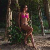 Geschiktheids vrouwelijke donkerbruine model dragende bikini en zonnebril die tegen boom leunen die haar haar op strand tegenhoud royalty-vrije stock foto's