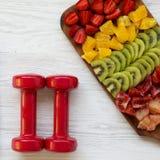 Geschiktheidsconcept, dieetplan Domoren en gehakte vruchten over witte houten oppervlakte, hoogste mening Vlak leg stock foto