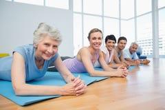 Geschiktheidsgroep die in rij bij yogaklasse liggen stock afbeelding