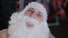Geschiktheidsinstructeur Santa Claus in de gymnastiek op de simulator, gezichtsclose-up stock videobeelden