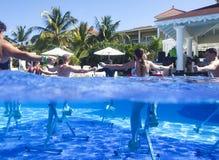 Geschiktheidsklasse die aquaaerobics op hometrainers in het hotel van de zwembadtoevlucht doen royalty-vrije stock fotografie