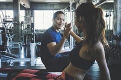 Geschiktheidsman en vrouw die elkaar een hoogte vijf na de opleidingssessie in gymnastiek geven Geschikt paar hoge vijf na traini royalty-vrije stock foto