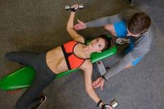 Geschiktheidsmeisje bij de gymnastiek met vrije gewichten en trainer Stock Fotografie