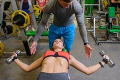 Geschiktheidsmeisje bij de gymnastiek met vrije gewichten en trainer Stock Afbeeldingen