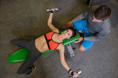 Geschiktheidsmeisje bij de gymnastiek met vrije gewichten en trainer Stock Afbeelding
