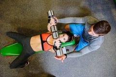 Geschiktheidsmeisje bij de gymnastiek met vrije gewichten en trainer Royalty-vrije Stock Fotografie