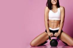 Geschiktheidsmeisje die met grote gewichtsdomoor het gelukkige glimlachen op roze uitwerken De sport werkt concept voor vrouw uit royalty-vrije stock afbeeldingen