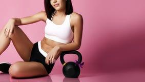 Geschiktheidsmeisje die met grote gewichtsdomoor het gelukkige glimlachen op roze uitwerken De sport werkt concept voor vrouw uit stock afbeelding