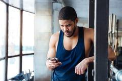 Geschiktheidsmens die slimme telefoon in de gymnastiek met behulp van Royalty-vrije Stock Afbeeldingen