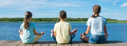 Geschiktheidsoefeningen, yoga die, drie Tienerjaren op de pijler dichtbij het water in openlucht zitten royalty-vrije stock fotografie