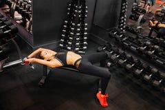 Geschiktheidsvrouw in de gymnastiek De oefeningen van de sporttraining met dumbbels royalty-vrije stock afbeelding
