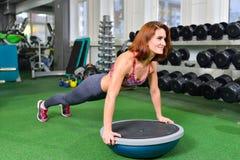 Geschiktheidsvrouw die doend de lichaamsgewichtoefening voor kernsterkte opleiding in gymnastiek met de trainer van het bosusaldo Stock Fotografie