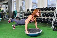 Geschiktheidsvrouw die doend de lichaamsgewichtoefening voor kernsterkte opleiding in gymnastiek met de trainer van het bosusaldo Stock Afbeelding