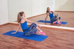 Geschiktheidsvrouw, die haar lichaam uitrekken, vóór training, voor de spiegel bij de gymnastiek stock afbeeldingen