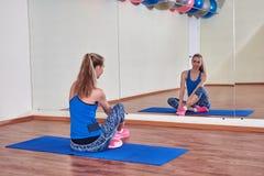 Geschiktheidsvrouw, die haar lichaam uitrekken, vóór training, voor de spiegel bij de gymnastiek stock foto's