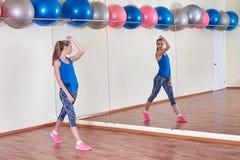 Geschiktheidsvrouw, die haar lichaam uitrekken, vóór training, voor de spiegel bij de gymnastiek De ruimte van het exemplaar stock afbeelding