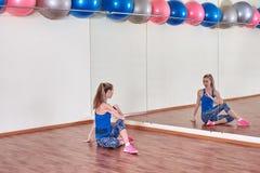 Geschiktheidsvrouw, die haar lichaam uitrekken, vóór training, voor de spiegel bij de gymnastiek De ruimte van het exemplaar stock foto's