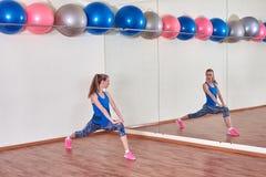 Geschiktheidsvrouw, die haar lichaam uitrekken, vóór training, voor de spiegel bij de gymnastiek De ruimte van het exemplaar stock foto