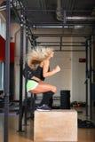 Geschiktheidsvrouw die op een houten doos springen, die in de gymnastiek, mening van de kant uitoefenen royalty-vrije stock foto's