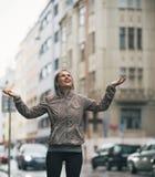 Geschiktheidsvrouw die regendalingen in de stad vangen Stock Afbeeldingen