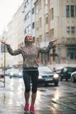 Geschiktheidsvrouw die regendalingen in de stad vangen Royalty-vrije Stock Fotografie