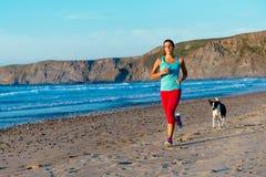 Geschiktheidsvrouw en hond die op strand lopen royalty-vrije stock afbeeldingen
