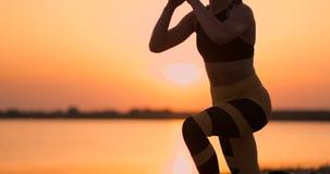Geschiktheidsvrouw het uitrekkende valt doen rekoefening uit De vrouwelijke atleet opleiding valt buiten rek in mooi uit stock footage