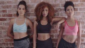 Geschiktheidsvrouwen die zich tegen bakstenen muur in gymnastiek bevinden stock videobeelden