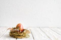 Geschilderd gekleurd paasei in een nest van vers hooi op een houten achtergrond royalty-vrije stock foto's