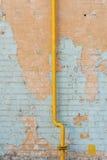Geschilderde bakstenen muur met een gaspijp Stock Foto's