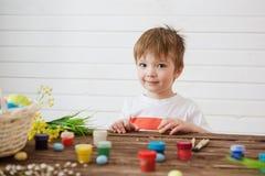 Geschilderde en verfraaide eieren voor Pasen Portret van leuke oude jongen 3 jaar Hij houdt een borstel en schildert paaseieren stock fotografie