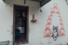 Geschilderde Grey Color Cat Looking Red-Beeldverhaalkatten op de Muur van de Straat van George Town Penang, Maleisië royalty-vrije stock afbeelding