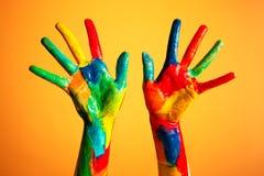 Geschilderde handen, kleurrijke pret. Oranje achtergrond Stock Foto