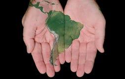 Geschilderde Kaart van Zuid-Amerika in Onze Handen Stock Foto's