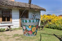 Geschilderde oude houten die plattelandshuisje, goed en emmer, met met de hand gemaakte geschilderde bloemen, Zalipie, Polen word stock foto