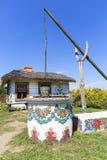 Geschilderde oude houten plattelandshuisje, goed en emmer, volkskunst, Zalipie, Polen stock fotografie