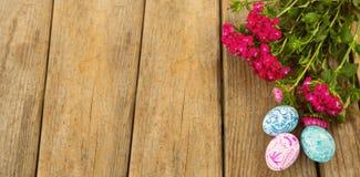 Geschilderde paaseieren en roze bloem op houten lijst Stock Foto