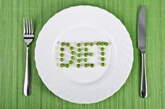 Geschirr - die Wortdiät der grünen Erbsen auf einer weißen Platte Stockfotos