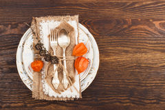 Geschirr mit orange Physalis und Tafelsilber Lizenzfreie Stockfotos