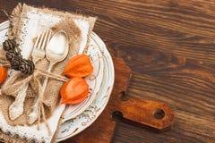 Geschirr mit orange Physalis und Tafelsilber Stockfotos