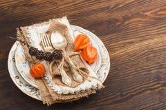 Geschirr mit orange Physalis und Tafelsilber Stockbilder