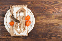 Geschirr mit orange Physalis und Tafelsilber Stockfoto
