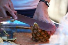 Geschlossen herauf die Hand des Chefs, der organische Ananas im Restaurant schneidet, Frucht abziehend Stockbilder