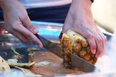 Geschlossen herauf die Hand des Chefs, der organische Ananas im Restaurant schneidet, Frucht abziehend Lizenzfreie Stockfotos