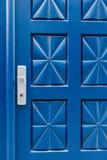 Geschlossene blaue Tür mit Muster- und Aluminiumgriff Lizenzfreies Stockfoto