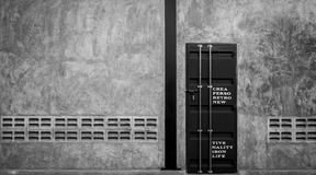 Geschlossene Eisentür auf Betonmauer mit Ventilator, Schwarzweiss-Szene Lizenzfreie Stockbilder