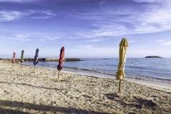 Geschlossene Farbregenschirme im Strand stockbild