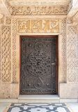 Geschlossene hölzerne gealterte Tür mit aufwändigen bronzierten Blumenmustern am Manial-Palast von Prinzen Mohammed Ali Tewfik, K Stockbild